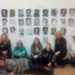 A group of artists sit below the portraits they drew.